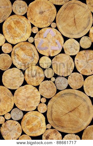 Stacked Logs, natural wood background with paper recycle symbol