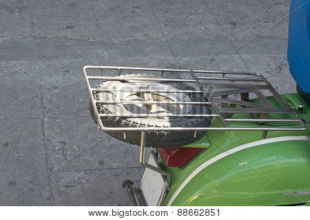 Black Spare Wheel Under Grill On Green Scooter Motorcycle