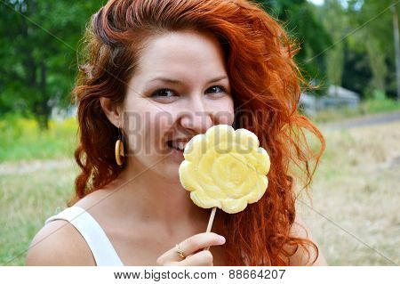 Beautiful young redhead woman smiling happily with a big flower shaped yellow lollipop