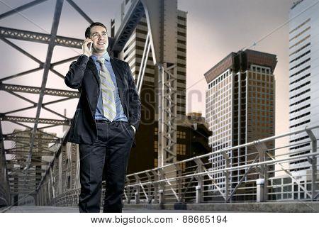 Businessman on the bridge speaking by phone