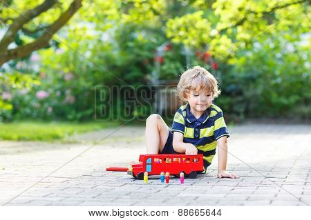 Little Blond Kid Boy In Colorful Clothes Playing With Red Wooden Bus