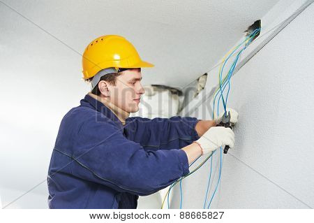 Male electrician at work laying wiring cable