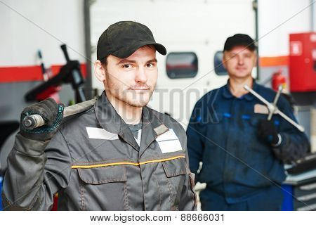 Two repairmans auto mechanic portrait in car auto repair or maintenance shop service station