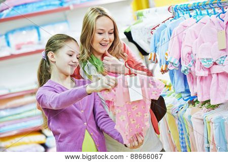 pregnant woman and little girl choosing newborn baby clothes during shopping at garments supermarket