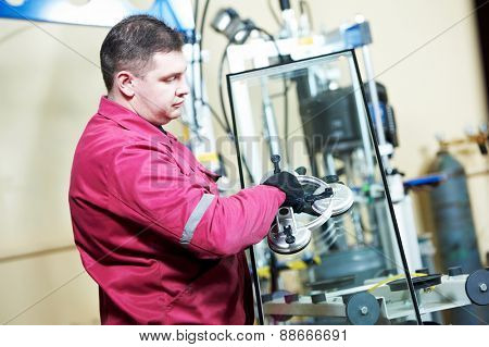 glazier worker with suction cup holding glass at double glazing window manufacture