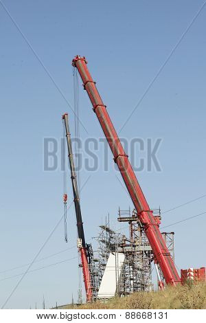 Red cranes on construction site