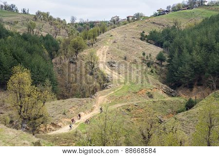 Group Of Mountain Bikers On A Steep Dirt Road Leading To A Mountain Village.