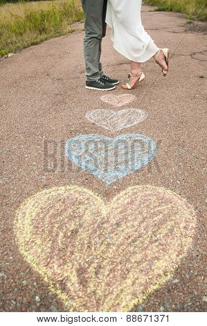 Heart Symbols Shaped With Crayons On Ground And Two People In Love