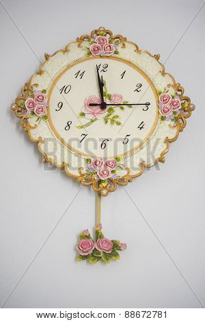 vintage wall clock on white wall.