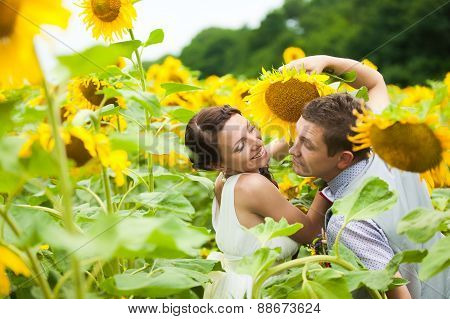 Happy Couple In Love Having Fun In Field Full Of Sunflowers