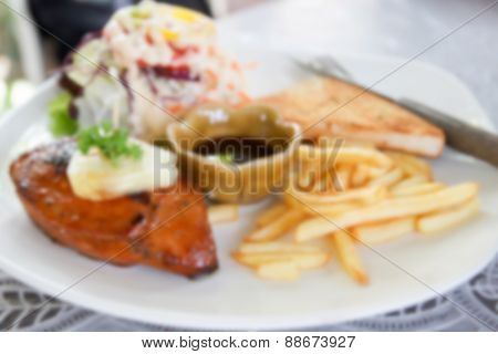 Blurry Defocused Image Of Chicken Steak With French Fried For Background
