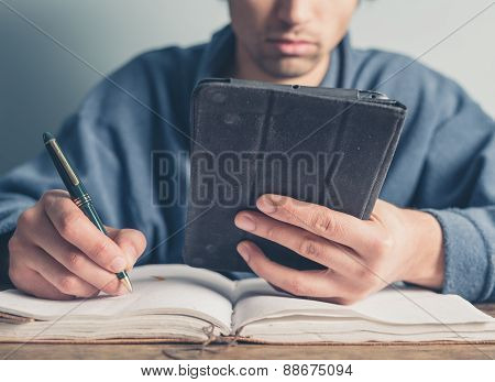 Man In Bathrobe Using Table And Taking Notes