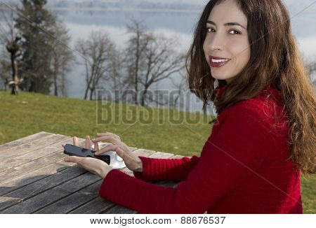 Woman At An Outdoor Restaurant Browsing With Her Smart Phone