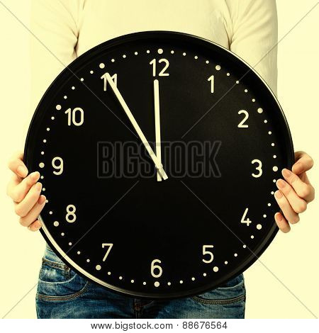 Woman holding an office clock