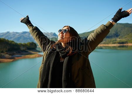 Happy Smiling Asian Woman Cheering Outdoors Under The Blue Sky. Woman Hiking Cheerful With Hands Up