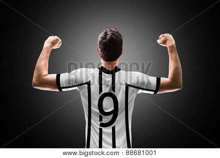 Soccer player on white and black t-shirt on black background