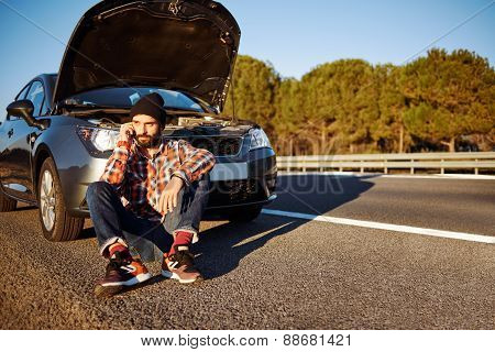Young Man Sits Near Car Talking On Cell Phone Because His Auto Broken. Beautiful bearded Man