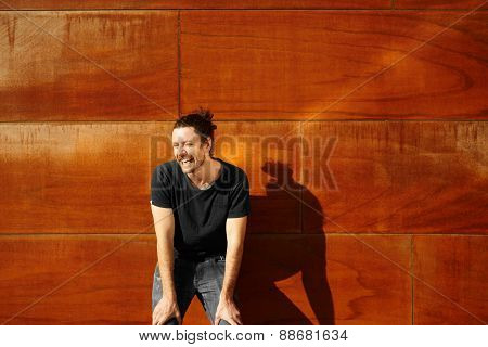 Hipster Urban Man Portrait. Casual Dressed Man In Black T-shirt And Washed Jeans Sly Smiling
