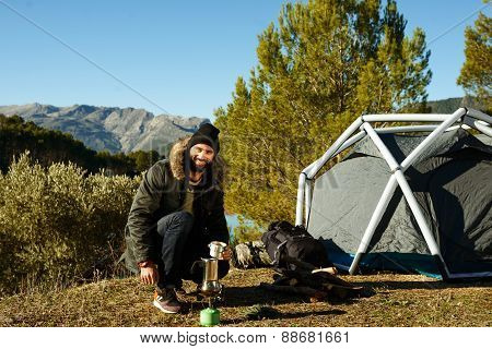 Adventure Hiking Man Drinking Coffee Near Tent. Smiling Happy Male Outdoors In Mountain Forest