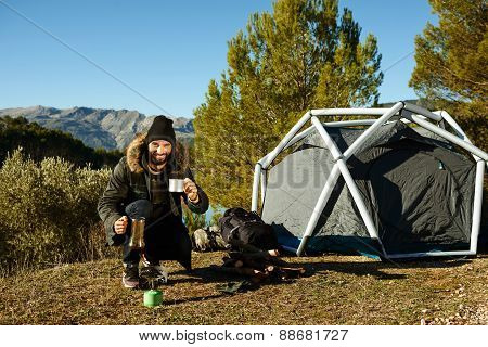 Man Camping Drinking Coffee Near Tent Smiling Happy Outdoors In Mountain Forest Enjoying Sun