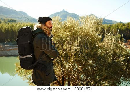 Adventure Hiking Man With Backpack.  Hikers Walking In Mountain Forest During Camping Travel Hike.