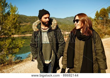 Happy Couple In Active Lifestyle Having Fun On Hike. Hikers Walking In Mountain Forest During Campin