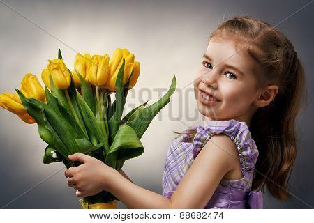 little girl and yellow tulips