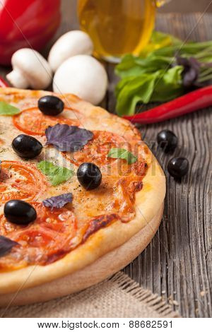 Traditional italian pizza margherita with tomatoes, olives and b