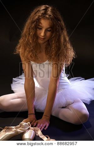 Portrait of daydreaming young ballet student sitting on floor in ballet costume.