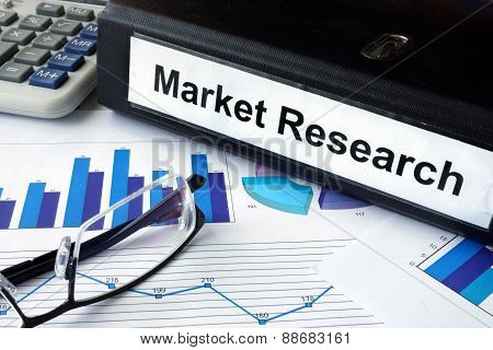 File folder with words Market Research and financial graphs.