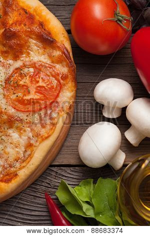 Pizza margherita with tomatoes, pepper, olive oil and mushrooms