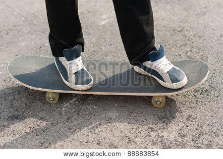 Skateboarder Feet In Sneakers On A Skateboard.