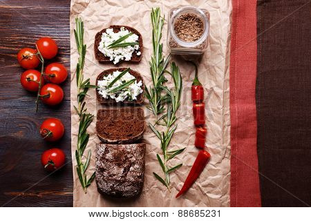Bread with cottage cheese, greens and tomatoes on paper on table top view
