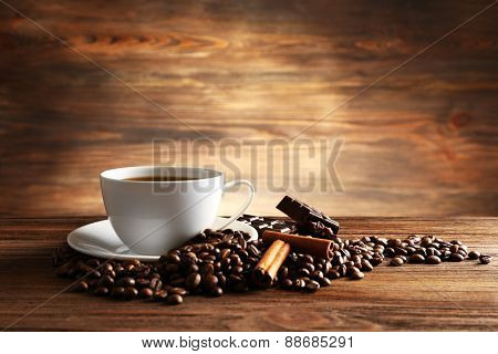 Cup of coffee with grains, chocolate and cinnamon sticks on wooden background