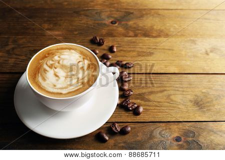 Cup of coffee latte art with grains on wooden background