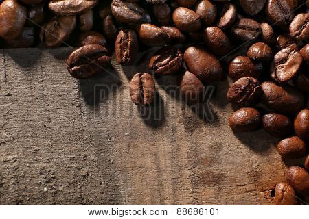 Pile of coffee beans on wooden table, closeup