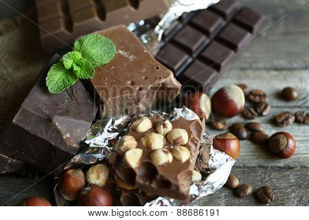 Set of chocolate with nuts on wooden table, closeup