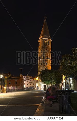 Nighttime view on Romanesque Cathedral's leaning bell tower with visitors