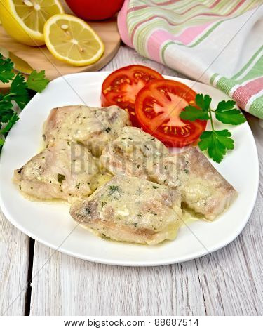 Fish stew in sauce on plate with lemon
