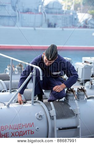 SEVASTOPOL, CRIMEA, UKRAINE - AUGUST 17, 2012: Seaman performs maintenance of  the torpedo tube on the Russian frigate