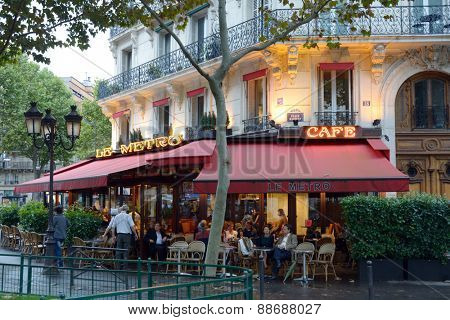 PARIS, FRANCE - SEPTEMBER 13, 2013: People resting in the street terrace of cafe Le Metro. Located on the place Maubert, the cafe provide the fine service for tourists