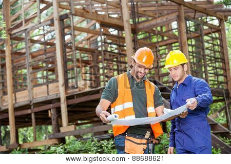 Male engineers analyzing blueprint outside incomplete wooden cabin at construction site