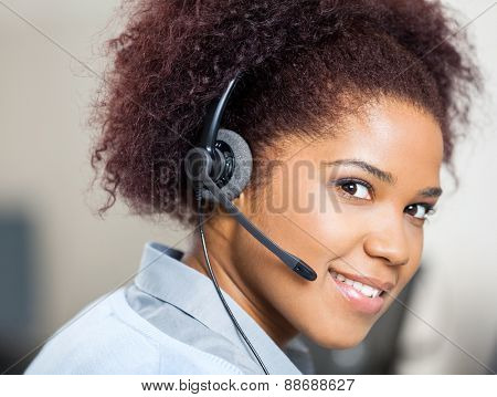 Portrait of confident female customer service agent wearing headset at desk in office