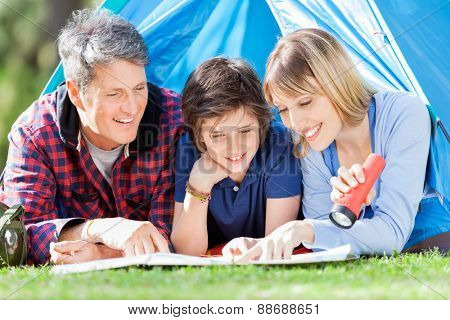 Smiling family looking at map in tent at park