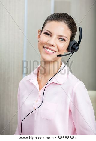 Portrait of smiling female customer service agent wearing headset in office