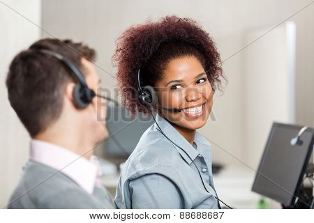 Happy customer service representatives talking with each other in call center