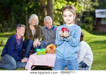 Portrait of girl holding apple while family in background at campsite