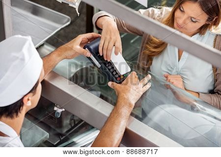 High angle view of mature female customer paying through smartphone at butchery