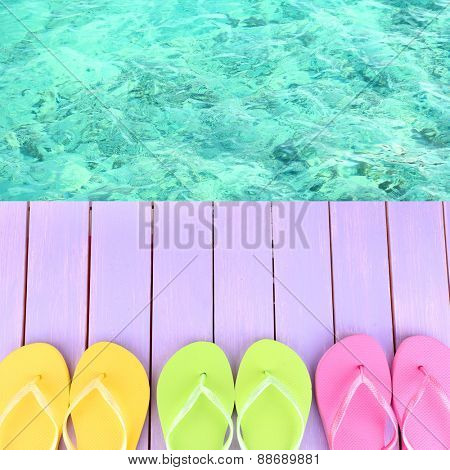 Female flip flops on wooden platform beside sea
