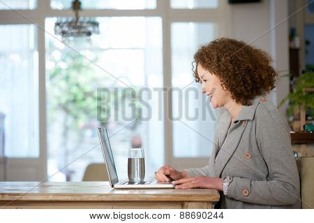 Older Woman Smiling And Using Laptop At Home